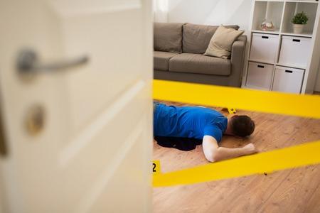 Murdel en plaats delict concept - dode man lichaam in bloed op de vloer liggen en kogel mouwen omheind door politie tape thuis kamer (geënsceneerde foto)