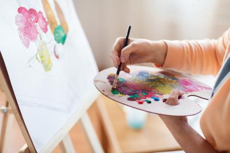 Kunst-, Kreativitäts- und Leutekonzept - nah oben vom Künstler mit Paletten- und Bürstenmalereistillleben auf Papier am Studio