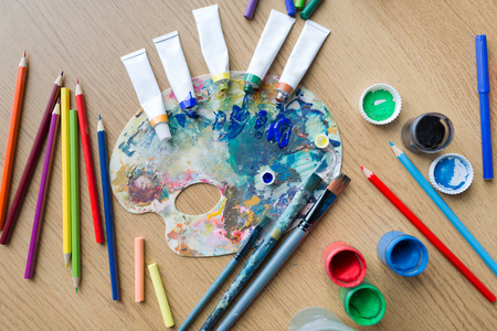 fine art, creativity and artistic tools concept - palette, brushes, paint tubes and gouache colors on table