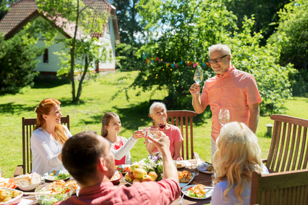 leisure, holidays and people concept - happy family having festive dinner at summer garden and celebrating