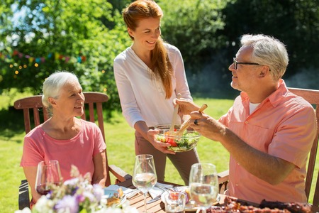 leisure, family and people concept - happy daughter offering salad to her senior father and mother at festive dinner or summer garden party Banque d'images