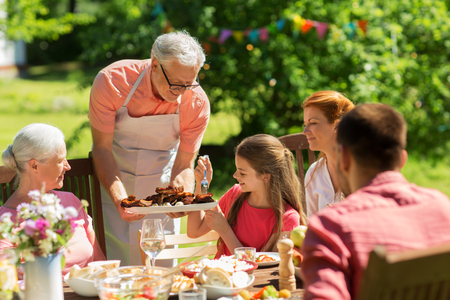 leisure, holidays and people concept - happy family having festive dinner or barbecue party at summer garden 스톡 콘텐츠