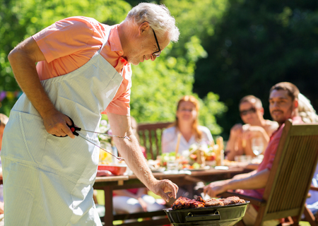 food, people and family time concept - senior man cooking meat on barbecue grill at summer garden bbq party Banque d'images