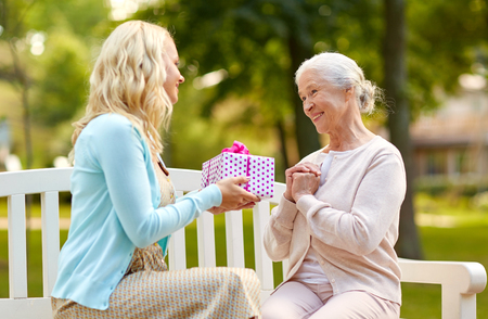 daughter giving present to senior mother at park