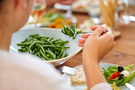 close up of woman eating green beans