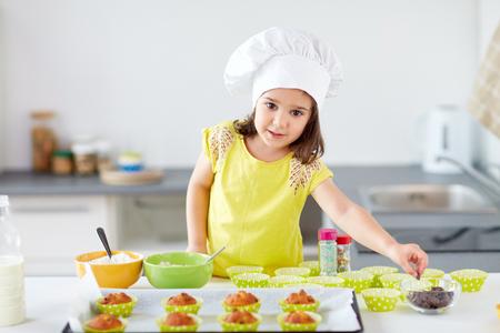 petite fille dans les chefs de chef cuisiniers de cuisson à la maison