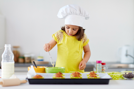 little girl in chefs toque baking muffins at home
