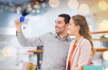 happy couple with smartphone taking selfie in mall Banque d'images
