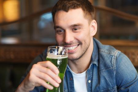 close up of man drinking green beer at bar or pub Stock Photo