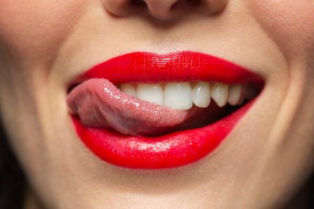 close up of woman with red lipstick licking lips 版權商用圖片