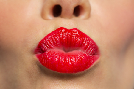 woman lips with red lipstick making kiss Stock Photo