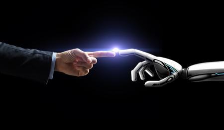 ロボットと人間の手は黒の上に光を点滅 写真素材