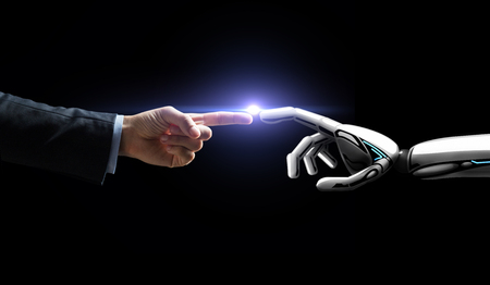 robot and human hand flash light over black Foto de archivo