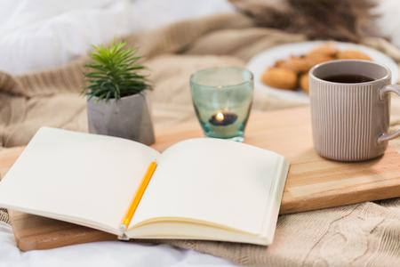 dagboek, thee en kaars in houder thuis