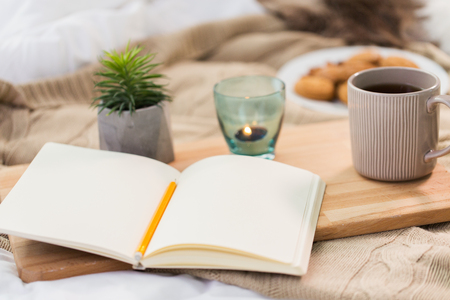 diary, tea and candle in holder at home