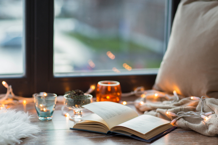 book, garland lights and candles on window sill