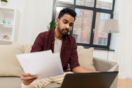 upset man with laptop and papers at home Stock Photo