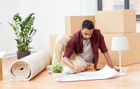 man met blauwdruk en dozen verhuizen naar nieuw huis Stockfoto