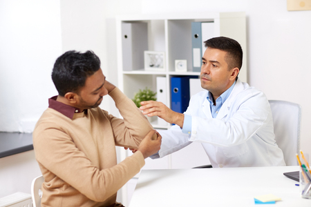 doctor and patient with arm injury at hospital