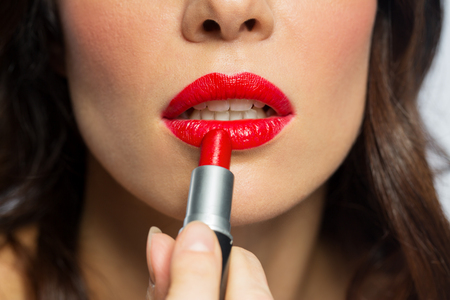 close up of woman applying red lipstick to lips Stock fotó