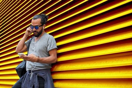 homme avec des écouteurs et smartphone sur le mur