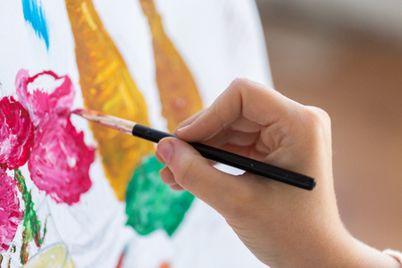 art, creativity and people concept - hand of artist with paint brush painting still life picture