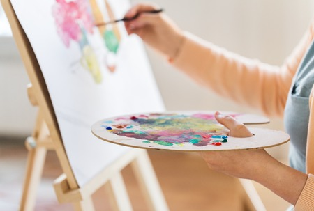 artist with palette and brush painting at studio Stock Photo