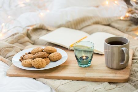 koekjes, thee en kaars in houder thuis