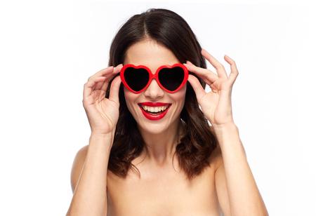Frau mit rotem Lippenstift und Herz formte Schattierungen Standard-Bild - 94040125