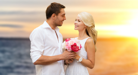 love, wedding and people concept - happy couple in white clothes with flowers over sea background