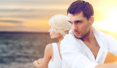 people and relationships concept - unhappy couple over sea background Stock Photo