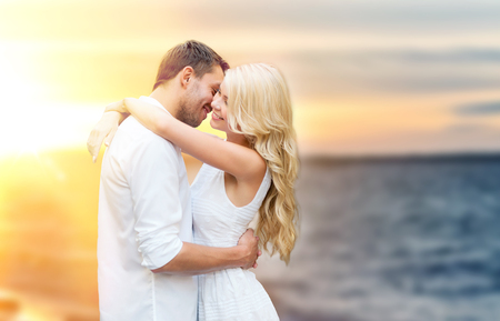happy couple hugging and kissing on summer beach