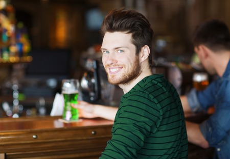 people, leisure and st patricks day concept - happy smiling young man drinking green beer at bar or pub