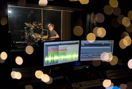 music, people and show business concept - sound mixing console with monitor screens and male musician playing drum kit at recording studio over lights Stock Photo