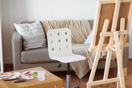 fine art, creativity and artistic tools concept - wooden easel and chair at home room or studio