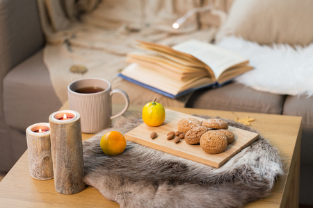 cookies, lemon tea and candles on table at home