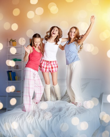 happy friends or teen girls having fun at home
