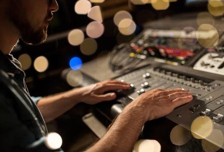 음악 녹음 스튜디오에서 믹싱 콘솔을 사용하는 사람