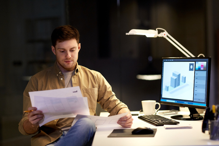 designer with papers working at night office