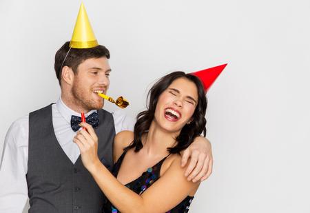 Pareja feliz con sopladores de fiesta divirtiéndose Foto de archivo - 94182868