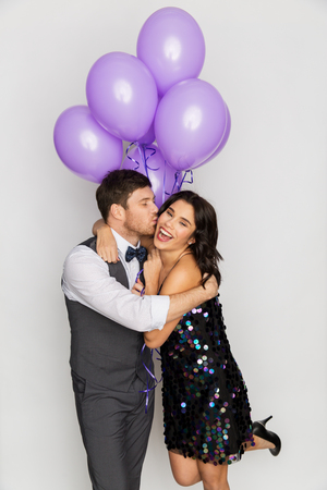 happy couple with violet balloons kissing at party Stock Photo