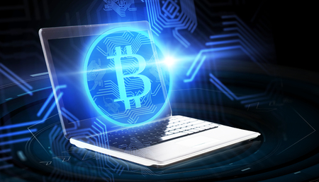 cryptocurrency, finance, business en toekomstig technologieconcept - laptopcomputer met bitcoinhologram op zwarte achtergrond