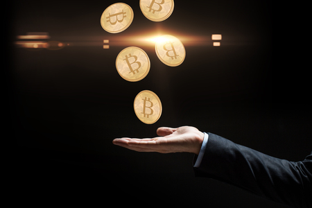 cryptocurrency, finance and business concept - close up of businessman hand with bitcoins over black background