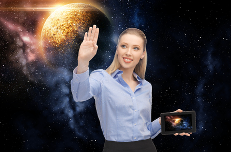 business, future technology and people concept - smiling businesswoman with tablet pc computer or navigator and planet hologram over space background