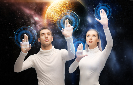 future technology and people concept - couple of scientists or astronauts with planet hologram over tablet pc computer at space laboratory Stock Photo