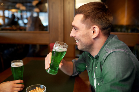 people, leisure and st patricks day concept - happy young man drinking green beer at bar or pub Stock Photo - 94242165
