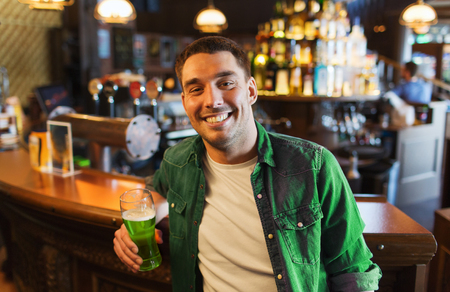 people, leisure and st patricks day concept - happy young man drinking green beer at bar or pub Stock Photo - 94242171