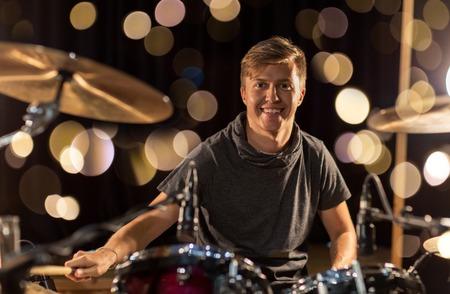 muziek, mensen, muziekinstrumenten en entertainment concept - mannelijke muzikant met drumsticks drumstel spelen op concert of studio over lichten