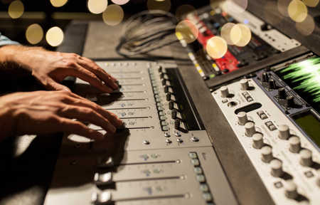 music, technology, people and equipment concept - man using mixing console in sound recording studio over lights Stok Fotoğraf
