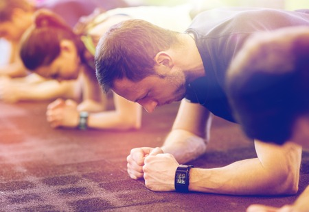fitness, sport, exercising, people and healthy lifestyle concept - man with heart-rate tracker at group training doing plank exercise in gym Foto de archivo